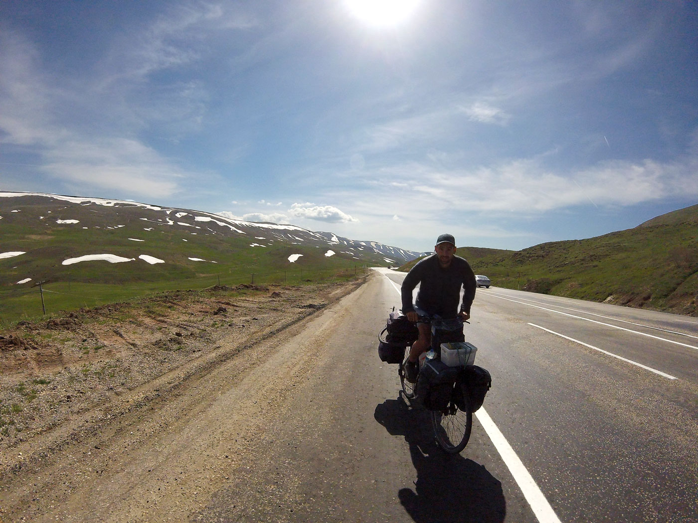 La Turquie à vélo, Arthur sur la route vers Erzincan avec les sommets enneigés. Cycling Turquey, Arthur on the road to Erzincan with snow-capped peaks.
