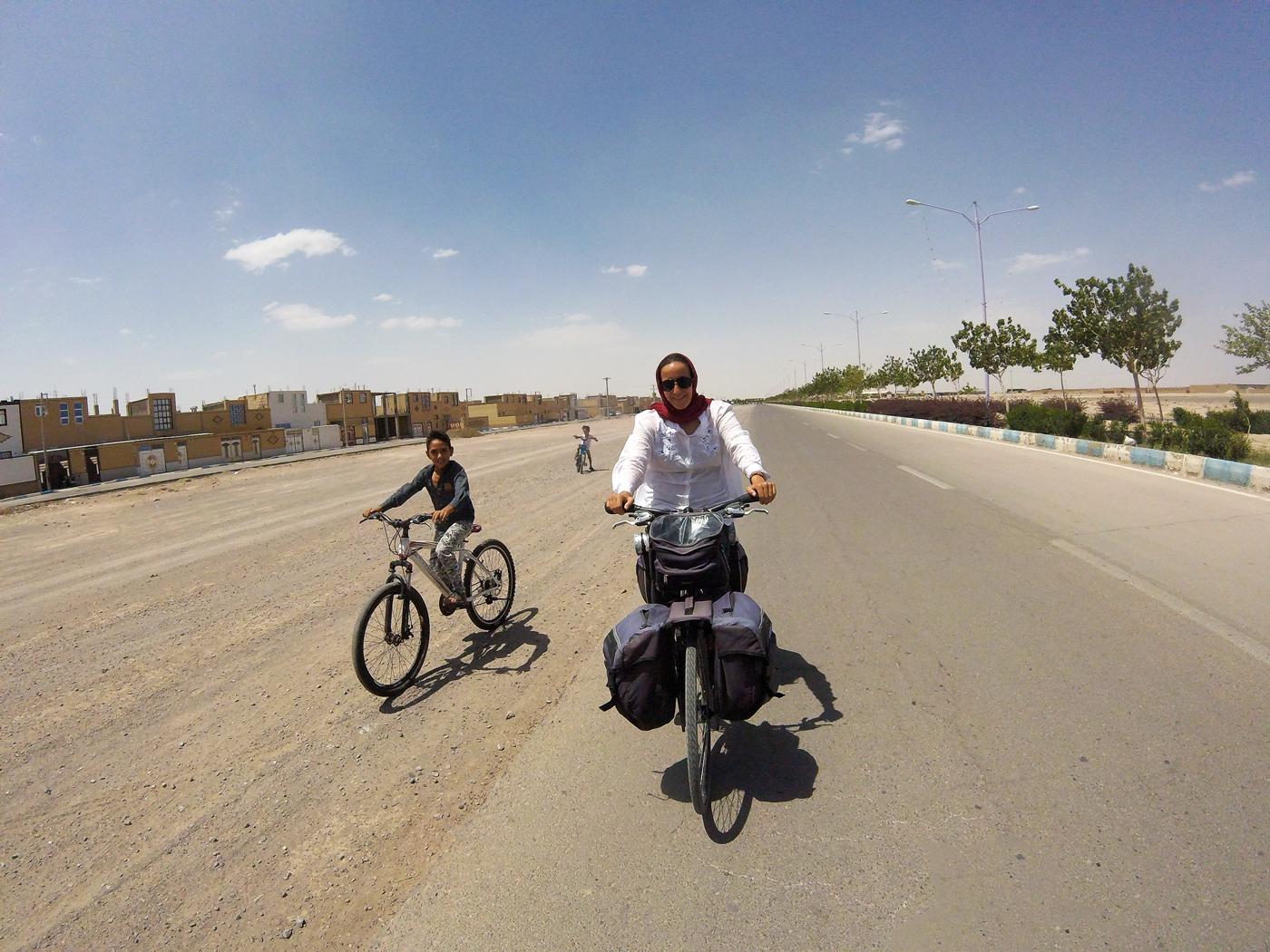 Voyage à vélo, traverser l'Iran à vélo, Yas à vélos avec des enfants à vélos sur la route de Varzaneh. Cycling travel, biketouring, cycling Iran, Yas cycling with children on bicycles on the road to Varzaneh.